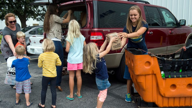 """I'd encourage anyone that can, to give supplies and donate money to this cause,"" said Anna Morgan (right), 19, a volunteer from Ocala, who accepts donations on Tuesday, October 11, 2016, delivered by Becky Kramer (left) and Lauren Johnson (center) and their children at Missionary Flights International in Fort Pierce. The organization has increased the number of relief flights to Haiti and the Bahamas since Hurricane Matthew devastated parts of the those countries. Donations will be needed for the next several weeks. They are especially low on batteries (AA, AAA, C and D) and non-perishable food items. They do not need adult clothing or water."