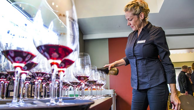 Charity Gerold, a hostess at Palette at Phoenix Art Museum, pours wine to give to the judges of the 2016 Arizona Republic Wine Competition, on Dec. 12, 2016.
