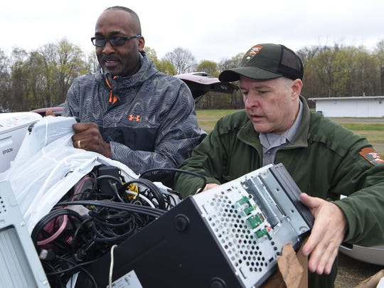 Mike Riegle, right, facility manager of both the Vanderbilt Mansion National Historic Site and the Home of Franklin D. Roosevelt National Historic Site, helps Anthony Watson, left, of the City of Poughkeepsie recycle old electronics during an Earth Day event at the Hyde Park Drive-In on Route 9 in Hyde Park.