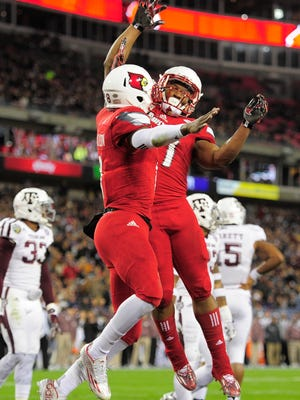 Louisville quarterback Lamar Jackson (8) celebrates the Cardinals' first touchdown with running back L.J. Scott (27)  in the first quarter of the Franklin American Mortgage Music City Bowl on Wednesday at Nissan Stadium.