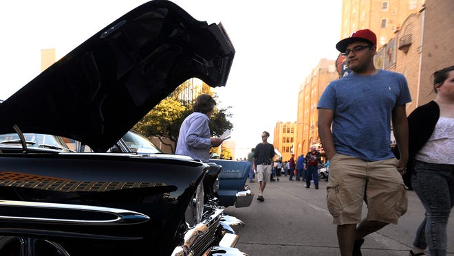 People check out the cars on display during the 2014 CarWalk.