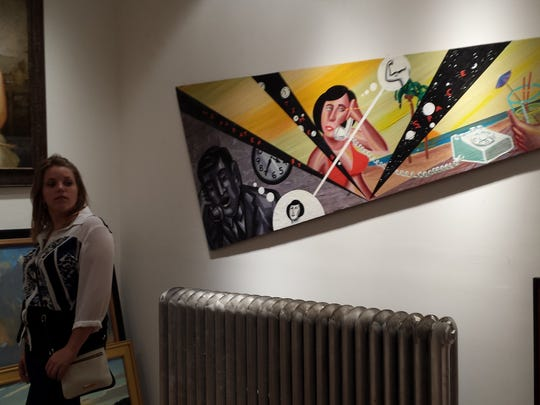 Burlington native Chelsea Johnson admires the art during First Friday in Philly. There are over 40 art galleries open to the public for free on the first Friday of every month.