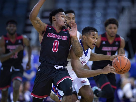 Evansville's Duane Gibson, right, is guarded by Arkansas State's Ty Cockfield at the Ford Center Friday night. The Purple Aces beat the Red Wolves 77-63.