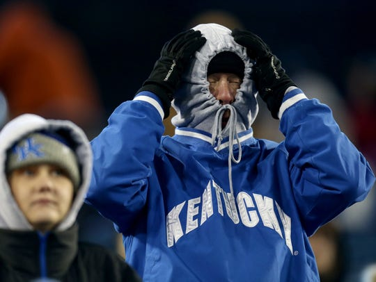 A bundled up Kentucky fan reacts to a player in the