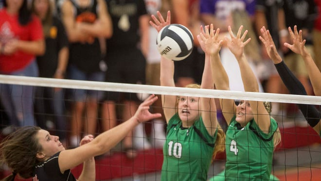 Yorktown's Tegan Seyring and Caitlin Shunneson try to block Wapahani's Estella Davis in the quarterfinals of the Delaware County Volleyball Tournament on Sept. 28 at Wapahani High School.
