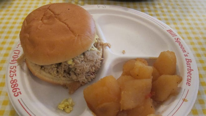 The barbecue sandwich is the go-to order at Bill Spoon's, with chopped pork from the slow-smoked whole hog and yellow, mustardy Eastern Carolina-style cole slaw, shown here with a side of barbecue potatoes.