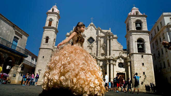 "A ""quinceanera"" poses during her photo session in front of the cathedral as tourists line up to enter the building, in Havana, Cuba Monday, March 14."
