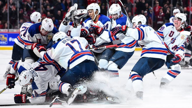 Members of Team USA jump on top of teammate Troy Terry after he scored the game-winning goal in the shootout.