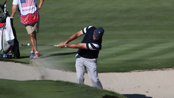 Phil Mickelson hits out of a bunker during the first round of the Presidents Cup Thursday at Liberty National.