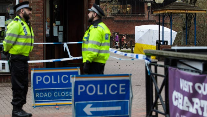 Police officers stand by a cordon as a forensics tent remains over a bench at the scene connected to the Sergei Skripal nerve-agent attack on March 13 in Salisbury, England.