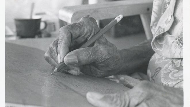 Folk artist Clementine Hunter making a picture.