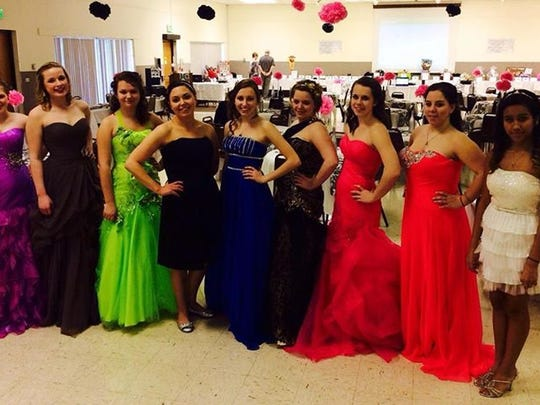 Models show some prom dresses at an All Dressed Up dinner fundraiser.
