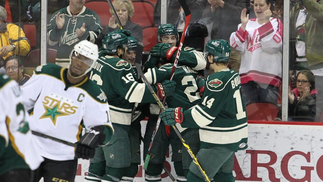 Iowa Wild players celebrate Zack Mitchell's first-period goal as Texas captain Maxime Fortunus skates away Tuesday at Wells Fargo Arena. The Wild lost to the Stars 4-3 for their fifth consecutive defeat.