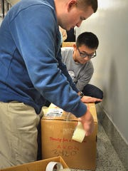 Dallastown High School students Clay Markey and Noah Pak tape up boxes of presents to be sent to military men and women for Christmas.