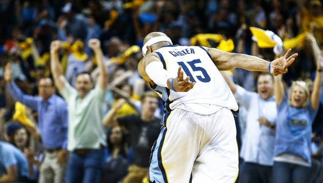 Memphis Grizzlies shooting guard Vince Carter celebrates a made 3-pointer against the San Antonio Spurs defense during second quarter action in the sixth game of their NBA first round playoff series at the FedExForum.