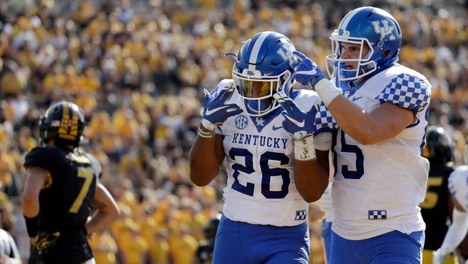 Kentucky running back Benny Snell Jr., center, is congratulated by teammate Greg Hart, right, after scoring on a one-yard touchdown run as Missouri safety Cam Hilton, left, looks away during the first half of an NCAA college football game Saturday, Oct. 29, 2016, in Columbia, Mo.