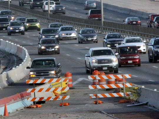 Drivers travel along Interstate 10 East at the Executive Center Boulevard exit amid concrete barriers adjacent to a construction area.