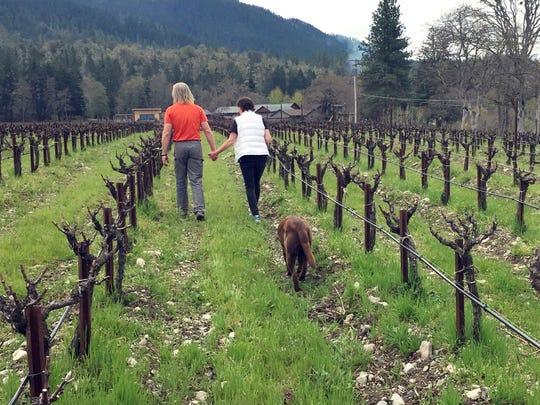 Bill and Barbara Steele walk through their vineyard outside Jacksonville, Ore.