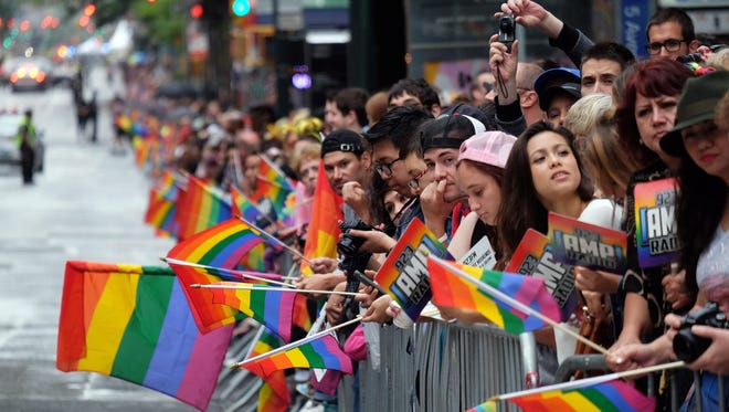 People hold rainbow flags as they wait for the start of the 2015 New York City Pride Parade in New York on June 28.