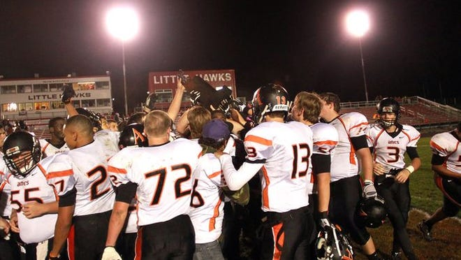 Ames teammates lift the Little Cy-Hawk trophy following the Little Cyclones' 44-20 win at City High on Friday.