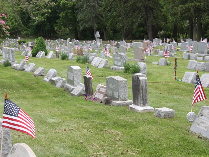 American Legion in Bound Brook decorate cemetery with flags.