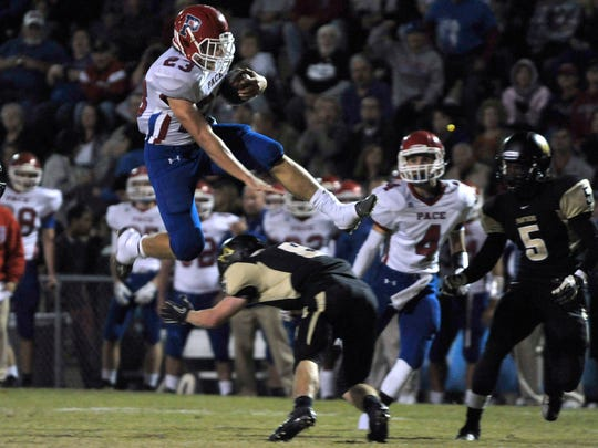 Quaide Weimerskirch, No. 23 of Pace High, leaps a Milton Panthers defender on his way to a big gain in yardage Friday night as the Pace Patriots traveled to Milton to take on the Panthers in one of the areas biggest high school rivalries.