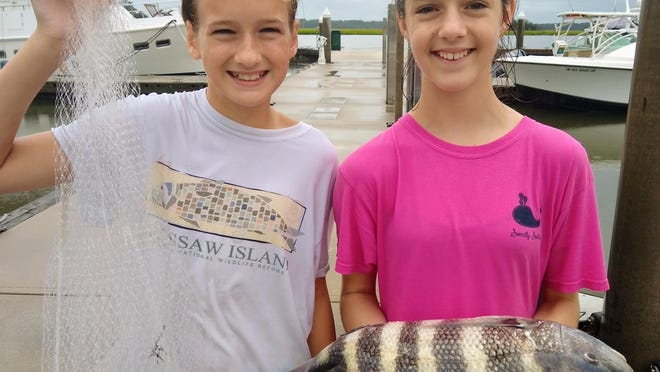 Sara Macdonald (left) and Margo Melroy of Isle of Hope caught this large sheepshead with a cast net off of a floating dock. These 12-year-olds can cast a perfect circle with a 10-foot net and have caught sheepshead each of the last two weekends (Aug. 23 and 30).