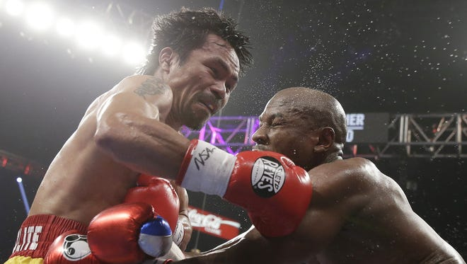 Manny Pacquiao, left, trades blows with Floyd Mayweather Jr., during their welterweight title fight on Saturday, May 2, 2015 in Las Vegas.