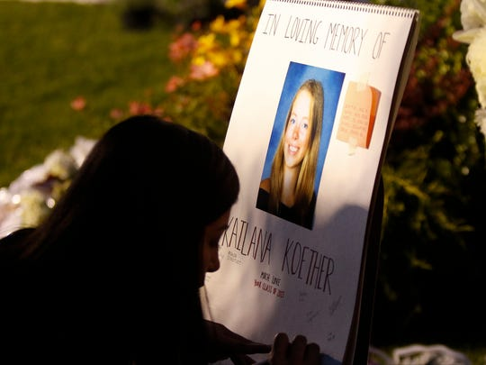 A Nyack High School student signs a card during a candlelight