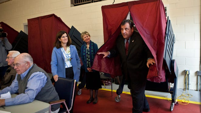 New Jersey Gov. Chris Christie exits a voting booth Tuesday as his wife, Mary Pat Christie, left, looks on in Mendham.