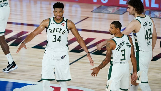 Milwaukee Bucks forward Giannis Antetokounmpo (34) celebrates the team's win over the Orlando Magic with guard George Hill (3) and center Robin Lopez (42) in an NBA basketball first round playoff game, Thursday, Aug. 20, 2020, in Lake Buena Vista, Fla.