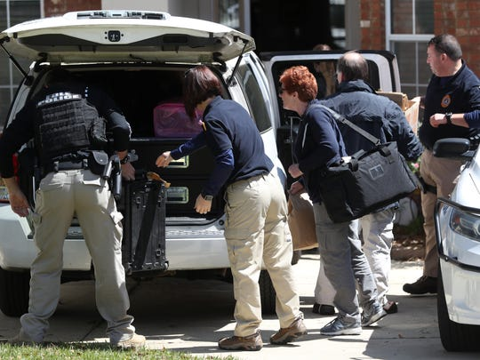 The FBI and local police remove items from a home owned