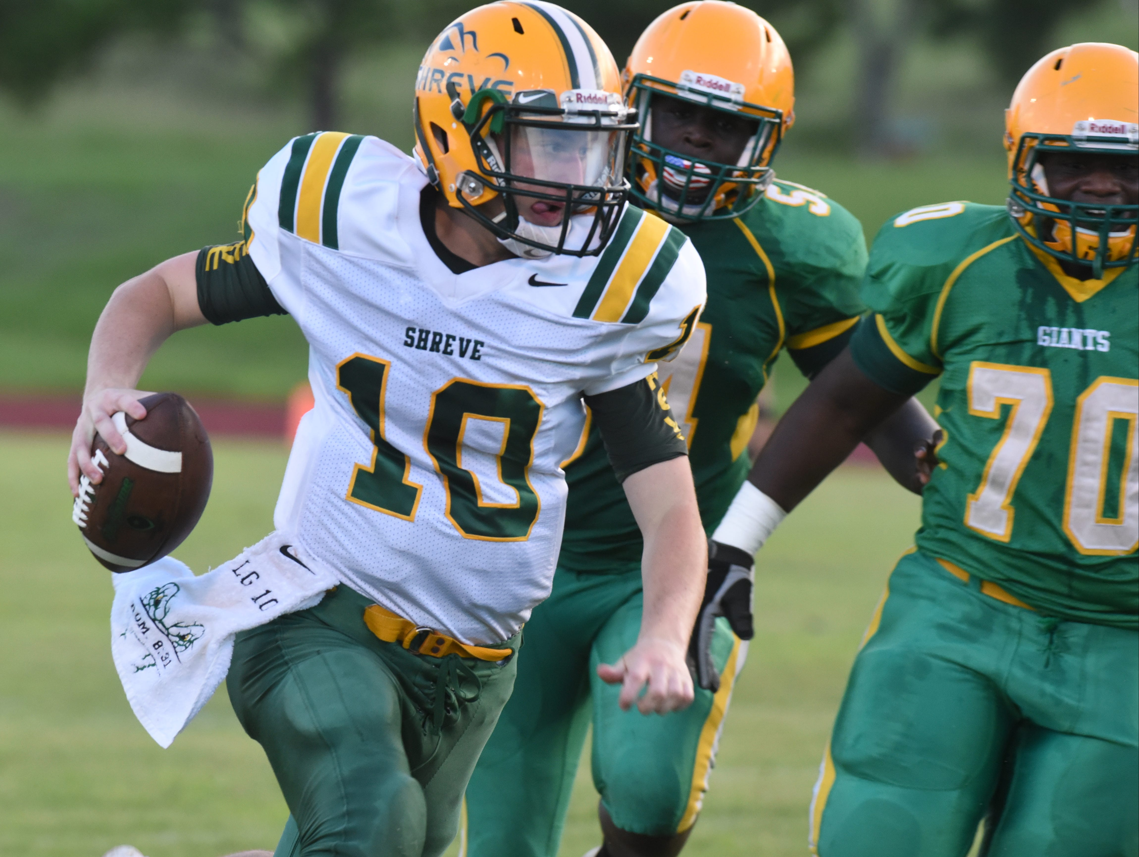 Capt. Shreve quarterback Lucas Grubb sprints from the backfield while being chased by Green Oak defenders.