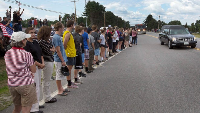 Area residents line the street in front of the ConVal Regional High School as the body of 18-year-old Cole Wohle passes by Tuesday, Aug. 2, 2016, in Peterborough, N.H. Wohle died Saturday after riding a horse in a rodeo in Castleton, Vermont. He suffered an unknown medical emergency.