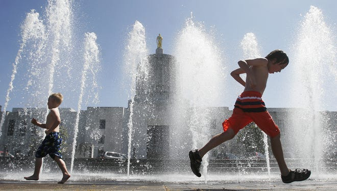 In this 2011 file image, children play in the Wall of Water fountain at the Capitol Mall in Salem.