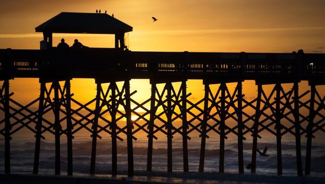 The sunrises behind Folly Beach Pier on Wednesday, April 12, 2017.
