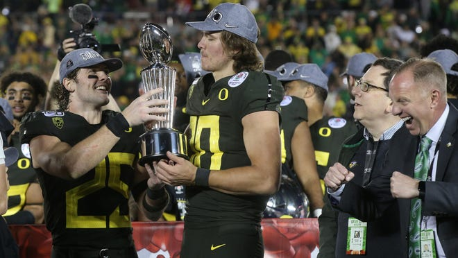 Oregon's Brady Breeze (25) hands the Rose Bowl trophy to Justin Herbert as they celebrate the Ducks' 28-27 win over Wisconsin on Jan. 1 as school President Michael Schill, second from right, and athletic director Rob Mullens, right, look on. [Chris Pietsch/The Register-Guard] - registerguard.com