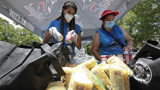 Volunteers Vanessa Sheffield, left, and Anakarina, who declined to give her last name, load food into bags at a food and mask distribution site put on by the Miami Marlins baseball organization Monday in Miami.