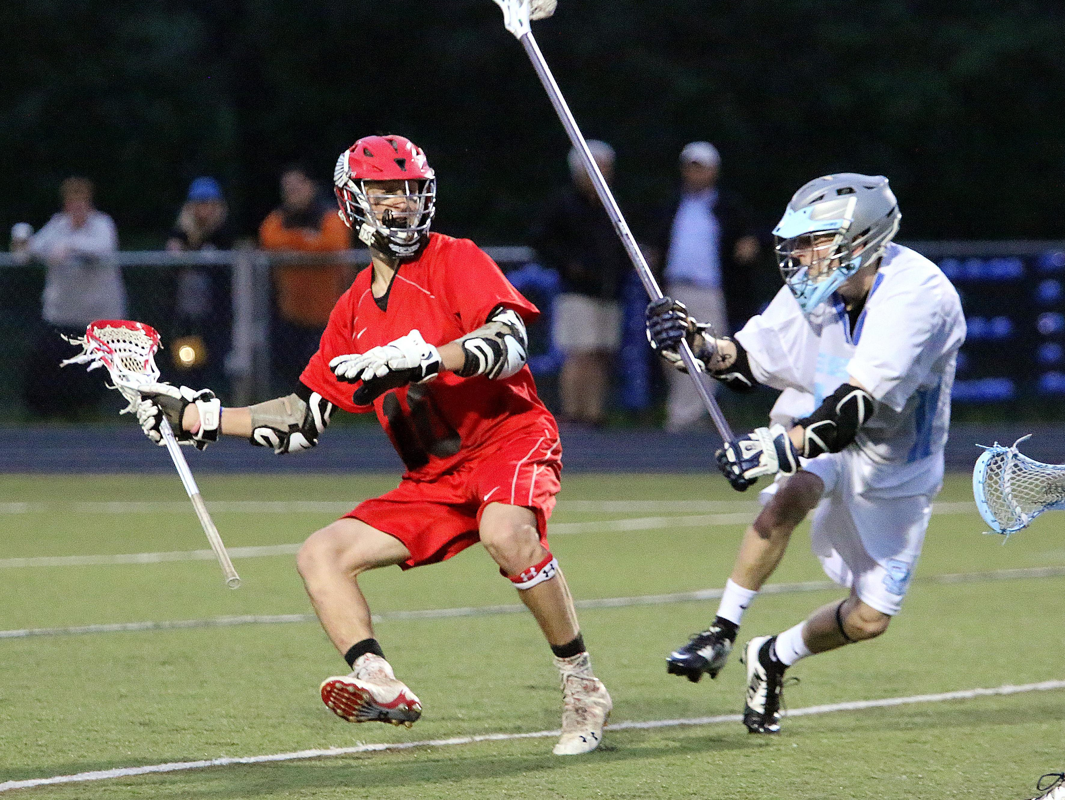Champlain Valley's Griffin Diparlo, left, evades a South Burlington defender during the Redhawks 6-5 win over the Rebels on Monday night.