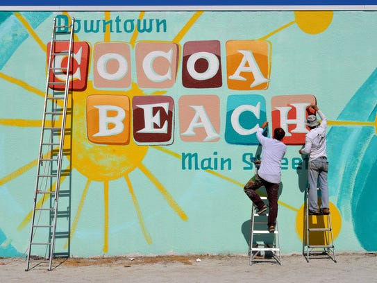 """Dr. Art is painting a giant """"Downtown Cocoa Beach Main Street"""" mural on the side of the former Diamond Castle on Atlantic Ave. in Cocoa Beach. Artists Hance Clay and David Rothman were busy Monday morning painting the retro style mural."""