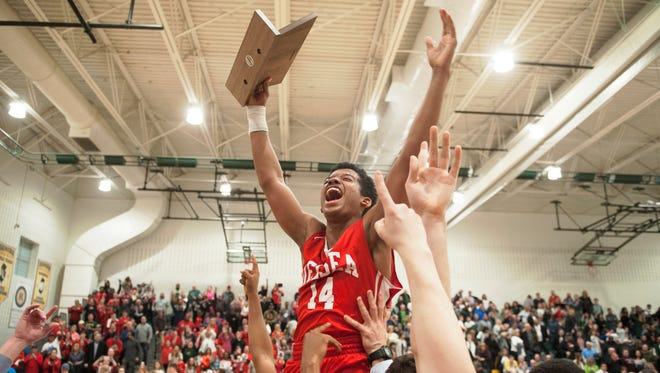 Delsea's Kolby Braxton hoists the trophy as he is lifted by teammates after Delsea defeated Seneca, 53-40, in the South Jersey Group 3 boys basketball final played at Seneca High School on Tuesday.  03.06.17