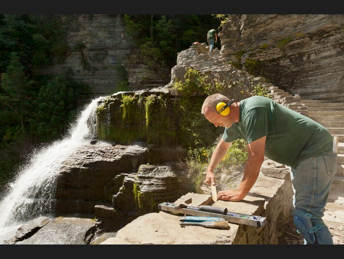 Roger Lyle of Pulteney, puts capstones onto the wall Tuesday afternoon along the upper section of the Gorge Trail next to the top of Lucifer Falls, background, at Robert H. Treman State Park. The trail which will reopen for the weekend has been closed since August of 2013.