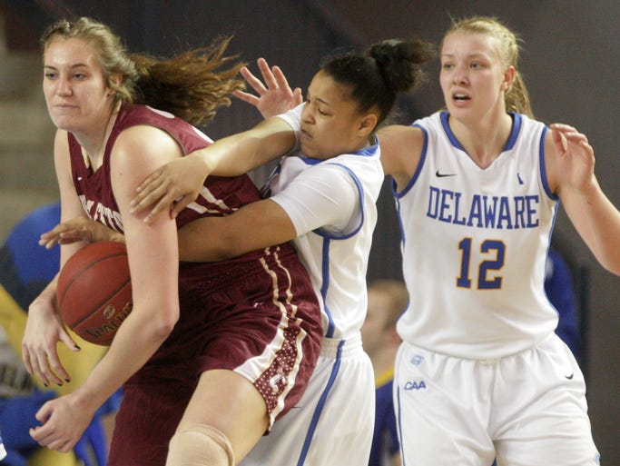 College of Charleston's Mikaela Hopkins (left) is fouled by Delaware's Erika Brown in the first half Friday, Feb. 14, 2014 at the Bob Carpenter Center. Delaware's Hannah Jardine is at right.