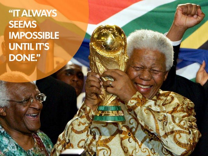 Former South African President Nelson Mandela holds the Jules Rimet World cup beside Capetown Archbishop Desmond Tutu, at the FIFA headquarters in Zurich on May15, 2004.