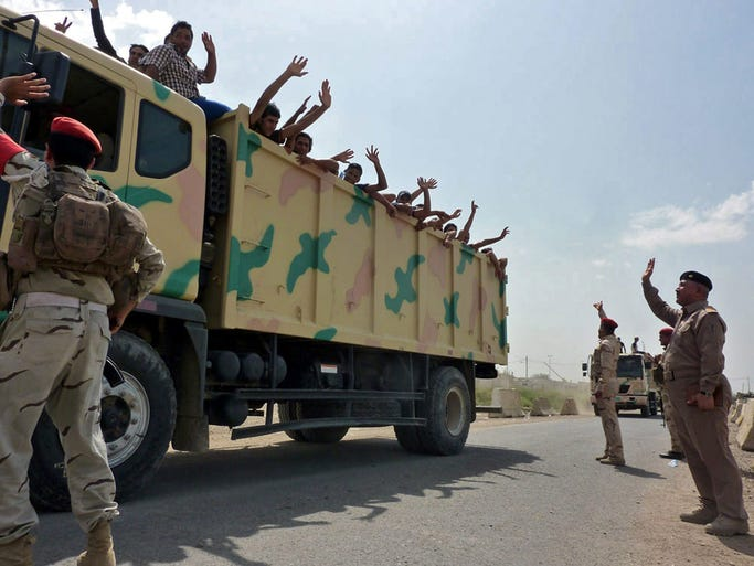 Iraqi military trucks transport Iraqi volunteers to Muthanna base in central Baghdad, on June 13. Sunni militants have captured at least one town in eastern Iraq, broadening their domination over portions of the country as they press south towards the capital Baghdad.