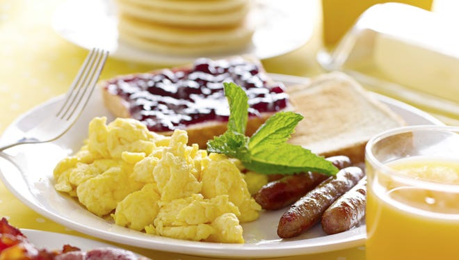 breakfast with scrambled eggs, sausage links and toast.