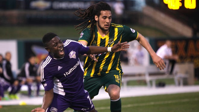 Louisville City Football's Kadeem Dacres, left reacts after being held by Rochester's Drew Ruggles.  Ruggles was given a yellow card for the play.  April 16, 2015