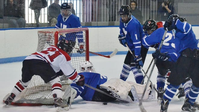 Rye forward Will Tutun attempts to fish out the puck before Hen Hud goalie Peter Gianatiempo covers it up during the first period on the Garnets' 7-0 win on Monday at Playland Ice Casino.