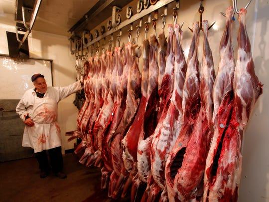 In this photo taken Nov. 17, 2014, veteran meat cutter