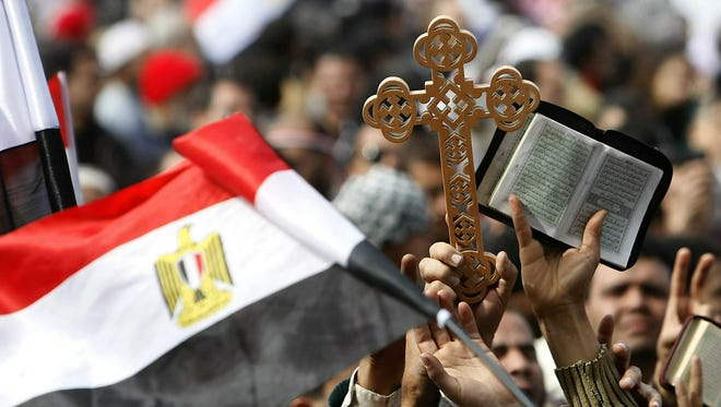 Egyptian Christians and Muslims wave a national flag as they brandish a cross and the Quran during a protest Feb. 6, 2011,  in Tahrir Square in Cairo.